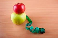 Manzana roja que pone en manzana verde cerca de la cinta métrica Foto de archivo