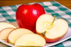 Manzana roja rebanada en la placa Imagen de archivo libre de regalías