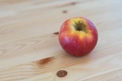 Manzana roja redonda en fondo de madera imagen de archivo