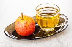 Manzana roja, taza con el zumo de manzana en plato marrón en la tabla de madera fotografía de archivo