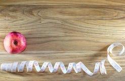 Manzana roja y centímetro en una tabla de madera Imagen de archivo