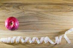 Manzana roja y centímetro en una tabla de madera Foto de archivo