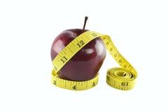 Manzana roja y medición amarilla aisladas en el fondo blanco Fotos de archivo