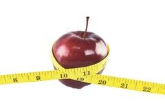 Manzana roja y medición amarilla aisladas en el fondo blanco Fotografía de archivo libre de regalías