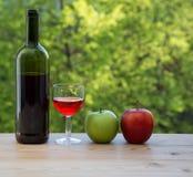 Manzana roja y verde de la copa de vino en la tabla Fotos de archivo