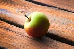 Manzana salvaje en la tabla de madera Imágenes de archivo libres de regalías
