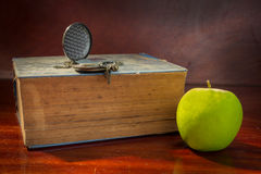 Manzana verde con el libro y el reloj antiguos Imagen de archivo