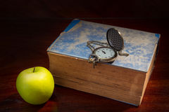 Manzana verde con el libro y el reloj antiguos imagen de archivo libre de regalías