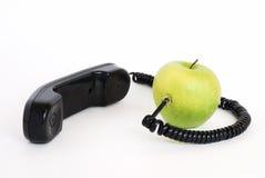 Manzana verde con el microteléfono y el alambre conectado Imágenes de archivo libres de regalías