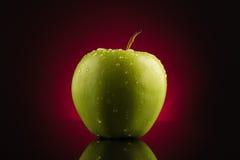 Manzana verde con gotas en fondo rojo Fotografía de archivo