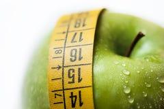 Manzana verde con la cinta de la medida Fotos de archivo