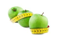 Manzana verde con la cinta métrica Imágenes de archivo libres de regalías