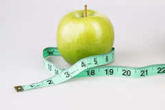 Manzana verde con la cinta métrica en blanco Foto de archivo