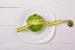 Manzana verde con la cinta métrica en una placa fotografía de archivo libre de regalías