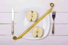 Manzana verde con la cinta métrica en una placa con el cuchillo y la bifurcación Venta, el por ciento imágenes de archivo libres de regalías