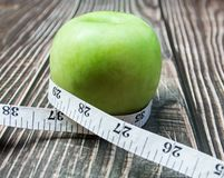 manzana verde con la medida en la madera fotos de archivo