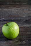 Manzana verde con las gotitas de agua en una tabla de madera Imagen de archivo libre de regalías