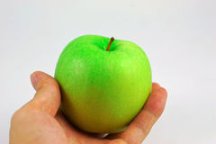 Manzana verde con las manos Foto de archivo