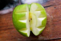 Manzana verde cortada decorativo/comida sana de las frutas y verduras/manzana tallada en el fondo de madera, cierre para arriba Imágenes de archivo libres de regalías