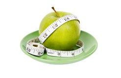 Manzana verde de dieta del concepto con la cinta de medición Fotos de archivo