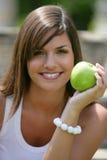 Manzana verde de la consumición adolescente Imagenes de archivo