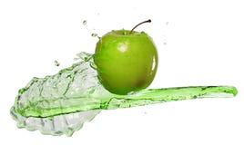 Manzana verde en corriente del jugo fotos de archivo