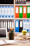 Manzana verde en la pila de libros al lado de un cuaderno y de los lápices en t Imágenes de archivo libres de regalías