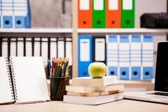 Manzana verde en la pila de libros al lado de un cuaderno y de los lápices en t Imagen de archivo