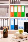 Manzana verde en la pila de libros al lado de un cuaderno y de los lápices en t Fotografía de archivo libre de regalías