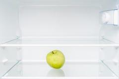 Manzana verde en refrigerador vacío imagen de archivo libre de regalías