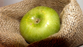 Manzana verde en un cuenco decorativo Foto de archivo