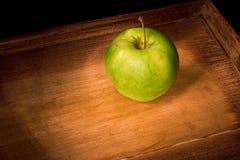Manzana verde en una bandeja de madera Foto de archivo libre de regalías