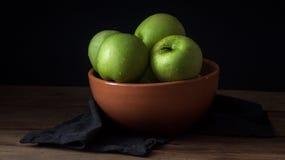 Manzana verde fresca con las gotitas del agua en cuenco contra fondo negro Foto de archivo