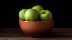 Manzana verde fresca con las gotitas del agua en cuenco contra fondo negro Fotografía de archivo