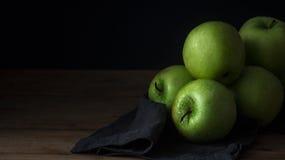 Manzana verde fresca con las gotitas del agua en cuenco contra fondo negro Imágenes de archivo libres de regalías