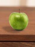 Manzana verde mojada en el escritorio Imagen de archivo libre de regalías