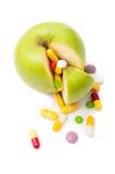 Manzana verde natural y diversas píldoras Fotografía de archivo