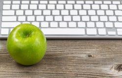 Manzana verde sana con el teclado en la mesa de madera rústica Fotos de archivo libres de regalías