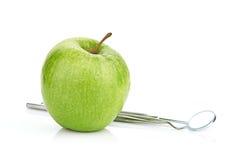 Manzana verde y herramientas dentales aisladas en blanco Fotografía de archivo libre de regalías