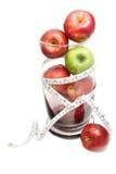 Manzana verde y manzana del rojo con la cinta métrica en bol de vidrio Imagenes de archivo
