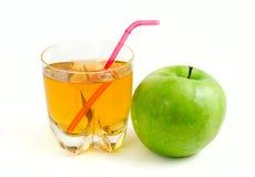 Manzana verde y un vidrio de zumo de manzana Imagen de archivo