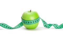 Manzana verde y una cinta de medición fotografía de archivo