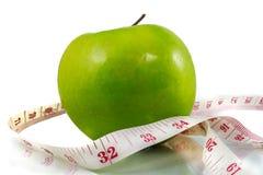 Manzana y cinta métrica verdes en el fondo blanco foto de archivo libre de regalías