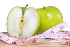 Manzana y cinta métrica verdes en el fondo blanco Imagenes de archivo