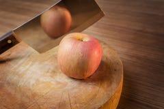 Manzana y cuchillo rojos en tabla de cortar de madera Imágenes de archivo libres de regalías