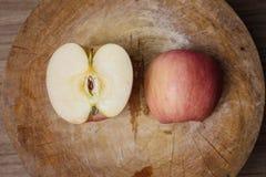 Manzana y cuchillo rojos en tabla de cortar de madera Foto de archivo libre de regalías