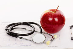Manzana y estetoscopio rojos en una carta del electrocardiograma (ECG) imágenes de archivo libres de regalías
