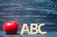 Manzana y letras rojas ABC en un fondo oscuro de un consejo escolar Fotografía de archivo