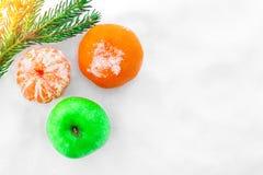 Manzana y mandarinas verdes en la nieve Rama de árbol de navidad en los rayos del sol Foto de archivo