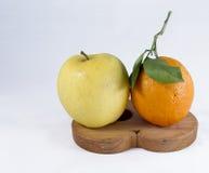Manzana y naranja amarillas en ayuda del pote Fotografía de archivo libre de regalías